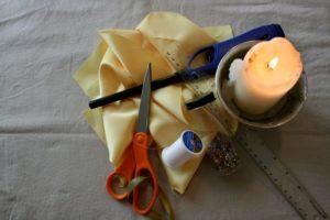 ткань, ножницы, свеча, нить с иглой и бусины